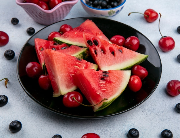 Front view slices of watermelon on a black plate with blueberries and cherries
