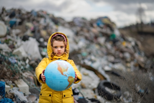 Front view of small child holding globe on landfill, environmental pollution concept.