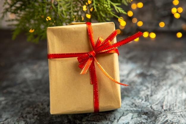 Vista frontale piccolo regalo luci di natale ramo di pino su sfondo scuro