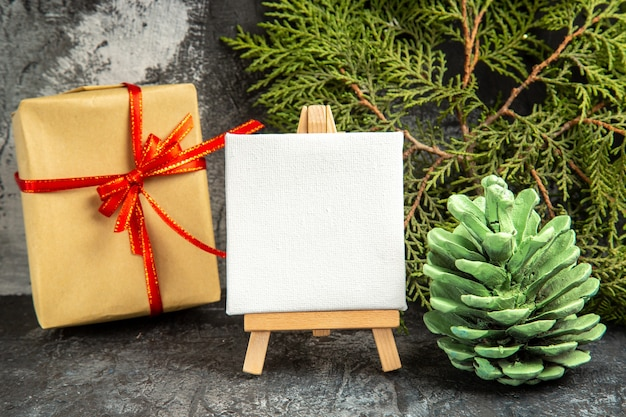 灰色の木製イーゼル松の枝に赤いリボンミニキャンバスで結ばれた正面図の小さな贈り物