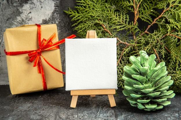Vista frontale piccolo regalo legato con nastro rosso mini tela su cavalletto in legno ramo di pino su sfondo grigio