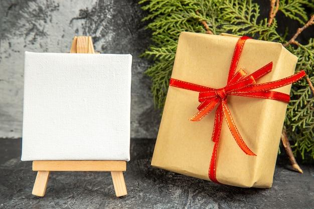 Вид спереди небольшой подарок, перевязанный красной лентой, рождественские конфеты, мини-холст, деревянный мольберт, сосновая ветка на сером