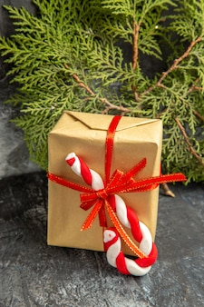 Front view small gift tied with red ribbon xmas candy pine branches on grey background