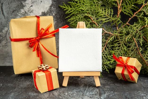 Вид спереди небольшие подарки, перевязанные красной лентой, мини-холст на деревянном мольберте, сосновая ветка на сером фоне