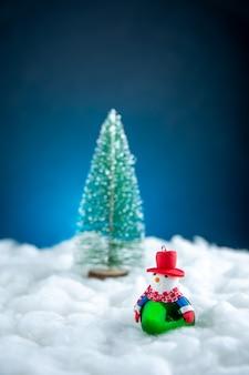 Vista frontale piccolo pupazzo di neve piccolo albero di natale su superficie blu