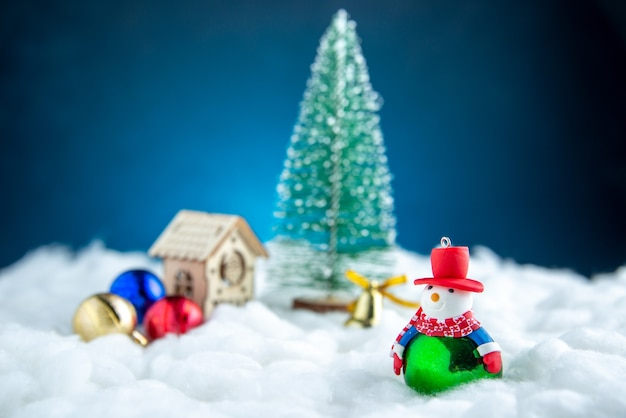 Front view small snowman xmas tree wood house ball toys on blue isolated surface