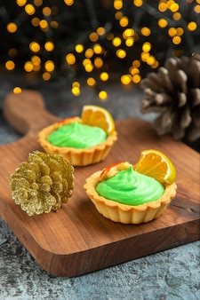 Вид спереди маленькие пироги на разделочной доске рождественские украшения на темной поверхности