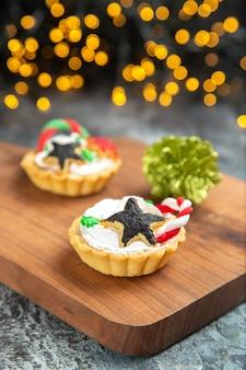 Вид спереди маленькие пирожные на сервировочной доске рождественские украшения на темной изолированной поверхности