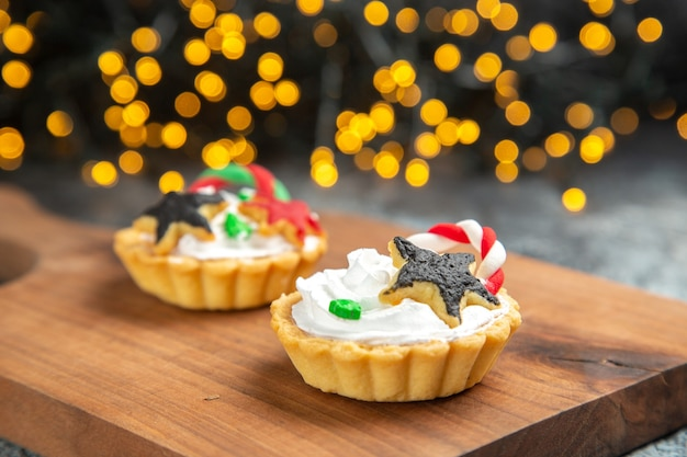 Front view small tarts on serving board on dark isolated surface xmas lights