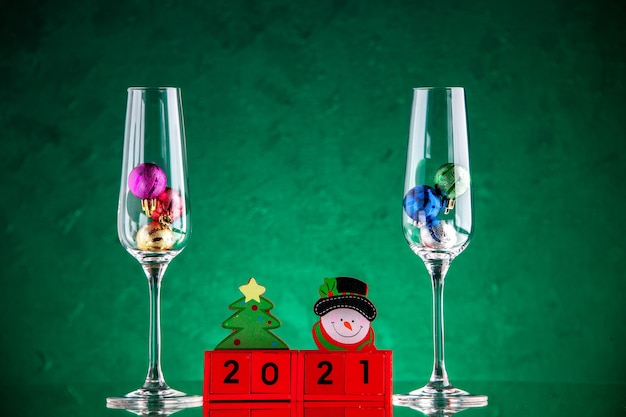 Front view small xmas balls in wine glasses wood blocks on green surface