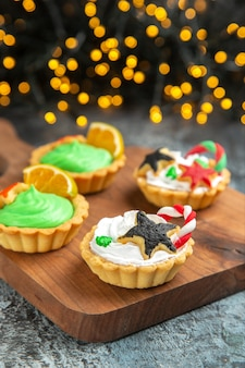 Front view small xmas tarts on cutting board on dark isolated surface xmas lights
