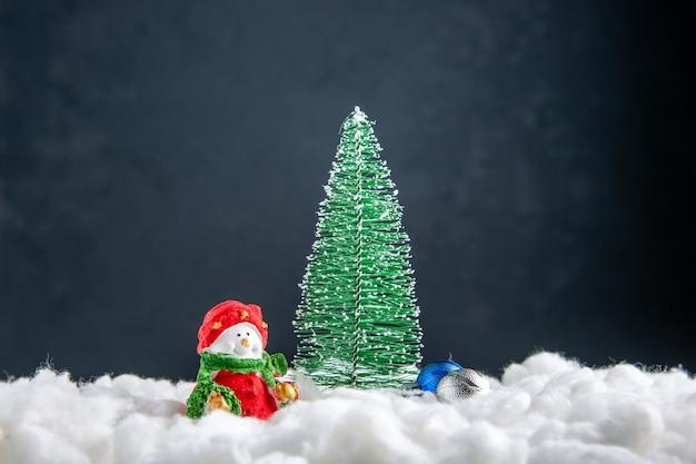 暗い表面の正面図の小さなクリスマスツリー雪だるまのおもちゃ