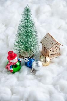 Vista frontale piccolo albero di natale ornamenti di natale piccola casa di legno su superficie bianca