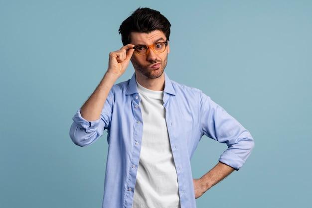 Vista frontale dell'uomo intelligente aggrappato ai suoi occhiali