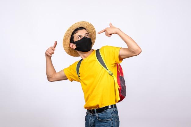 Giovane intelligente vista frontale con maschera e maglietta gialla che punta le dita su se stesso