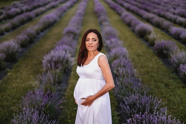 Front view of smiled brunette caucasian pregnant woman dressed in white dress, touching belly in lavender field.