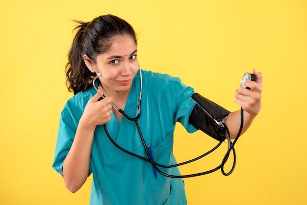 Vista frontale sorrise medico femminile in uniforme che tiene il dispositivo di misurazione della pressione sanguigna su sfondo giallo