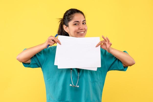 Vista frontale sorrise dottoressa con documenti su sfondo giallo