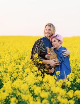 Vista frontale della ragazza sorridente con il suo ragazzo, in piedi tra il campo con il gatto e distogliendo lo sguardo