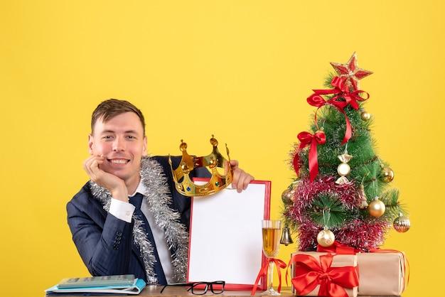 Vista frontale del bel ragazzo sorrise seduto al tavolo vicino all'albero di natale e regali su giallo