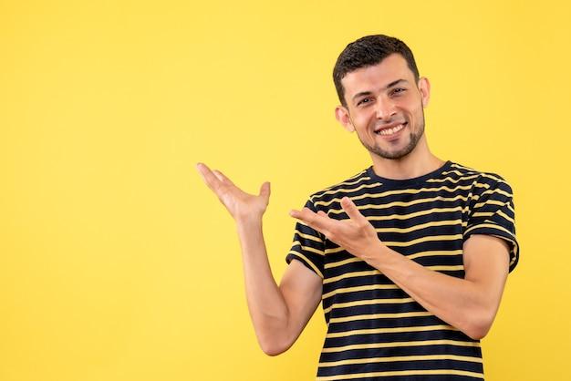 正面図は、黒と白の縞模様のtシャツ黄色の孤立した背景でハンサムな男性を微笑んだ