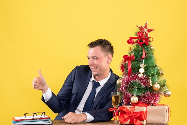 Front view of smiled man making thumb up sign sitting at the table near xmas tree and gifts on yellow