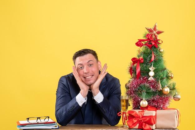 Vista frontale dell'uomo sorrise che mette le mani al suo mento che si siede al tavolo vicino all'albero di natale e regali sul giallo
