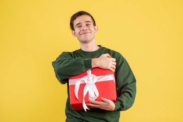 Вид спереди улыбающийся мужчина в зеленом свитере, стоящий на желтом