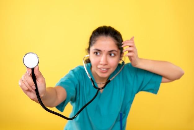 正面図は、黄色の孤立した背景に聴診器を保持している制服を着た女性医師に微笑んだ
