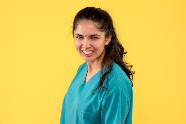正面図は黄色の背景に立っている制服を着た女医師に微笑んだ