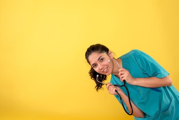 正面図は黄色の背景に聴診器を保持している若い女性医師に微笑んだ