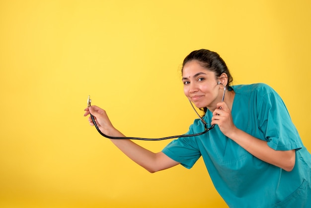 Vista frontale sorrise giovane dottoressa con stetoscopio su sfondo giallo