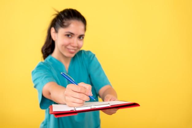 正面図は黄色の背景にクリップボードを保持している若い女性に微笑んだ