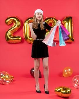 赤のショッピング バッグの風船を保持している黒のドレスを着た笑顔の若い女性の正面図