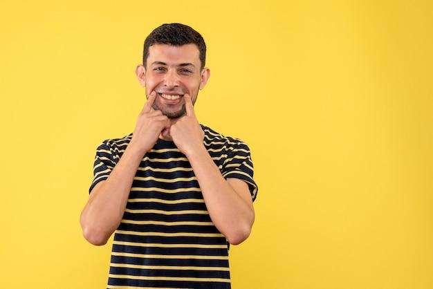 正面図は、黒と白の縞模様のtシャツ黄色の孤立した背景で若い男性を微笑んだ