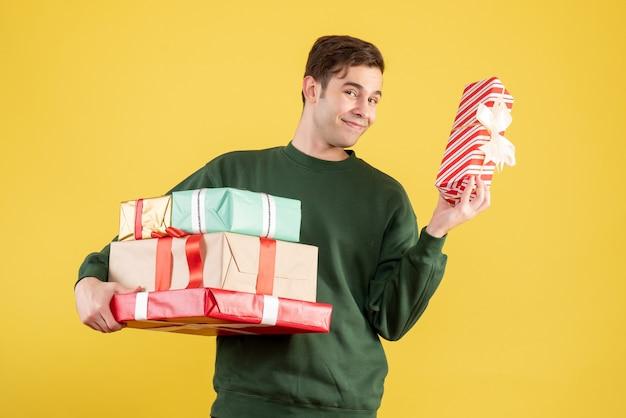 正面図は黄色の上に立っている新年の贈り物を保持している緑のセーターで若い男を微笑んだ