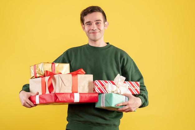 正面図は黄色の上に立っている緑のセーターで若い男を微笑んだ