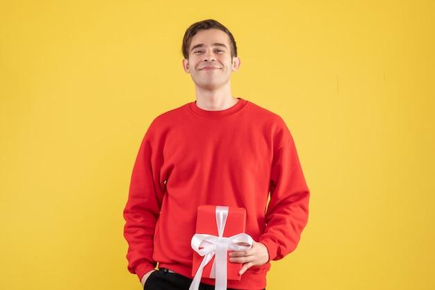 正面図は黄色の上に立っている赤いセーターで若い男を微笑んだ