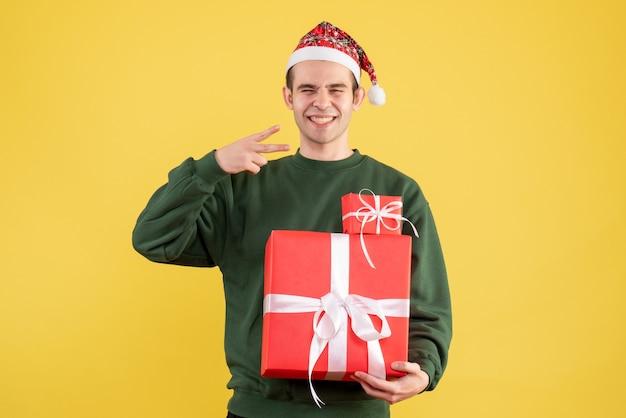 正面図は黄色の上に立っている勝利のサインを作るクリスマスプレゼントで若い男を微笑んだ
