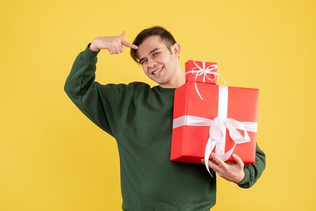 Front view smiled young man with xmas gift pointing at gifts standing on yellow