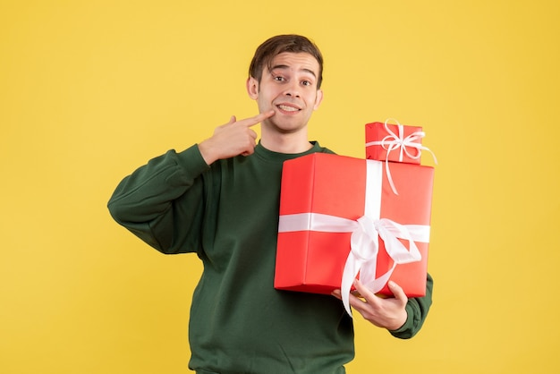 Front view smiled young man with xmas gift pointing at his smile standing on yellow