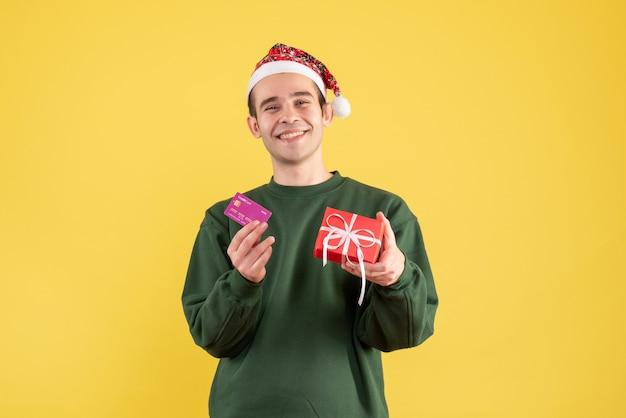 正面図は黄色の上に立っているクリスマスプレゼントと若い男を微笑んだ
