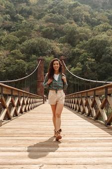 Front view smiley adventurier woman on bridge