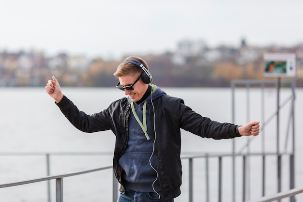 Front view smiley blonde man listening to music and dancing
