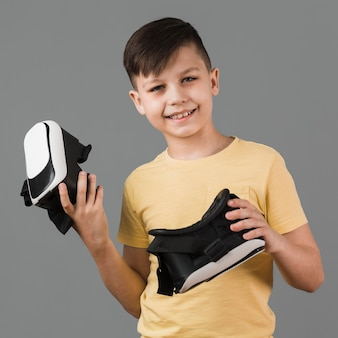 Front view of smiley boy holding two pairs of virtual reality headsets