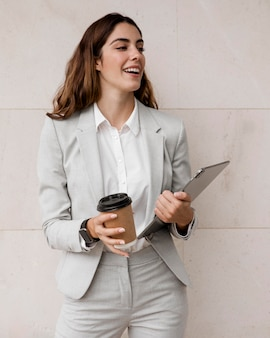Front view of smiley businesswoman holding tablet and coffee cup