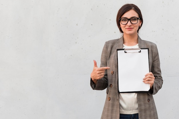 Front view of smiley businesswoman pointing at notepad outdoors