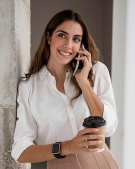 Vista frontale della donna di affari di smiley parlando al telefono mentre beve il caffè