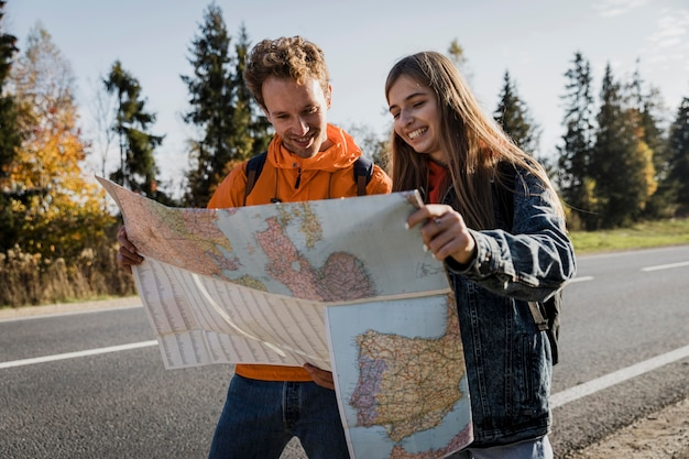 Front view of smiley couple consulting map while on a road trip