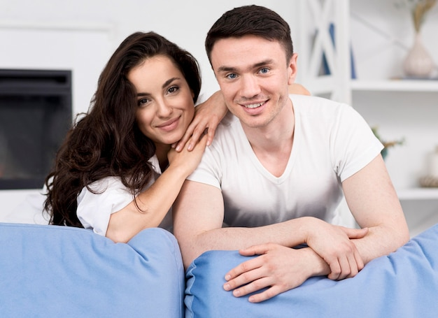 Front view of smiley couple posing together on couch